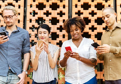 Four people in a line connecting their phones at a networking industry event.