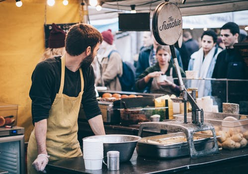 man in apron stands at his cafe stall known for high quality service